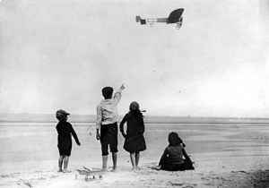 """Right side long view from below and slightly to the rear of BlŽriot XI in flight; four children watch from beach in foreground. Original French caption: Le monoplan XI de Bleriot pique droit vers la c™te anglaise. [""""BlŽriot's monoplane XI heads right for the English coast."""" This would seem to indicate that the aircraft is being piloted by Louis BlŽriot himself.]"""